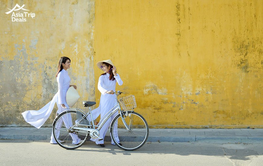 Young girls in Vietnamese traditional clothes ao dai in Hoi An old town