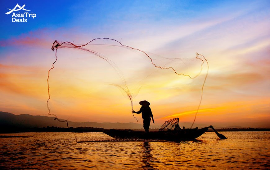 Silhouette of traditional fishermen throwing net fishing lake at sunrise time