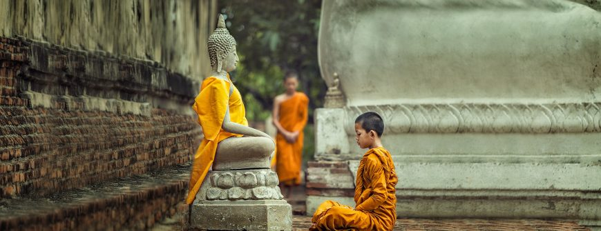 Young monk meditating in front of a Buddha statue