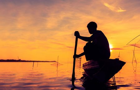 Fishermen on his boat at twilight